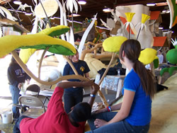 Holy Family Grade School Builders Club members meticulously place some organic materials on a Rose Bowl Parade float.